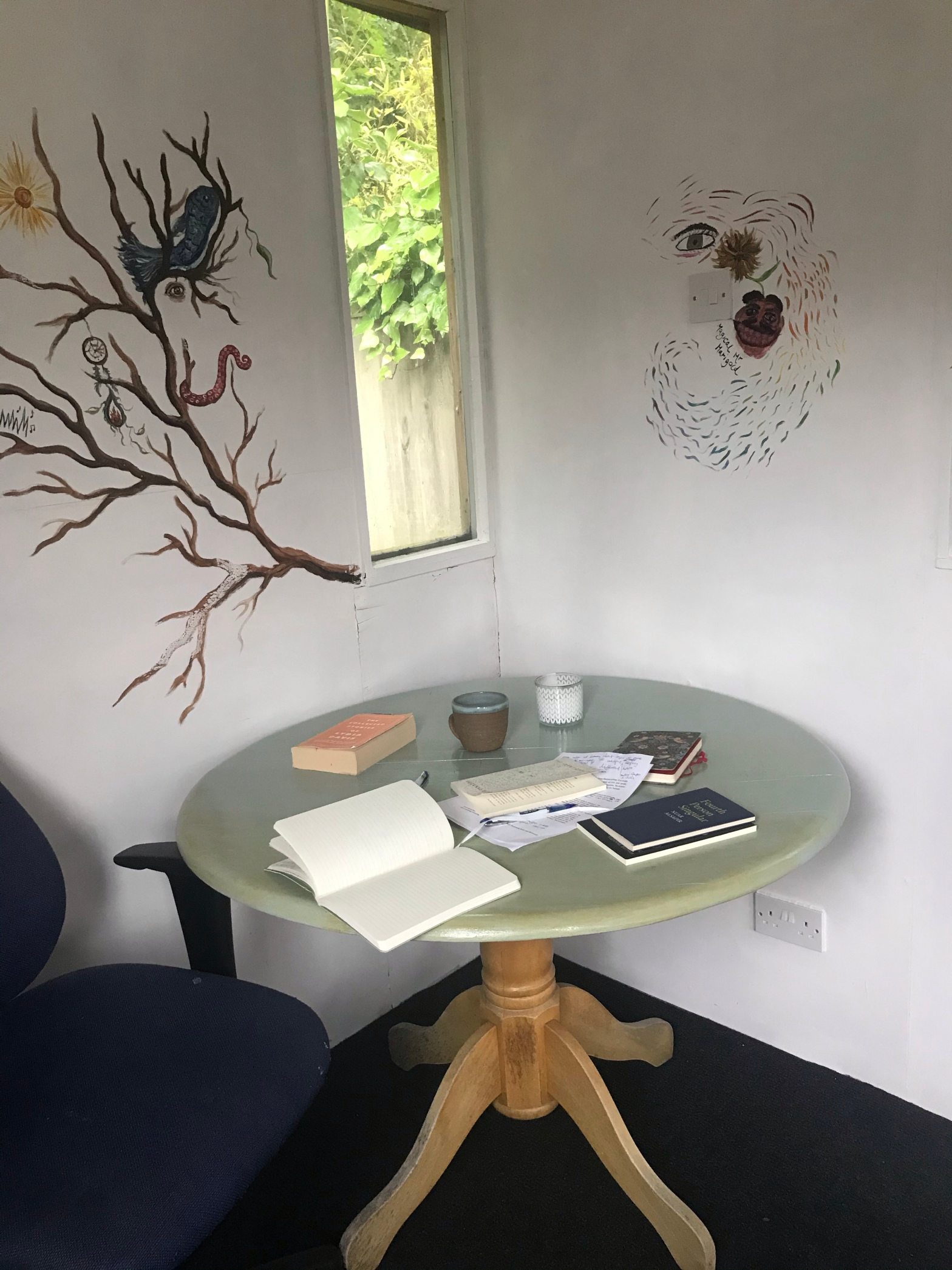 The image is of a table that has books and notebooks on it. It is by a small window and there are drawings on the adjacent white walls.