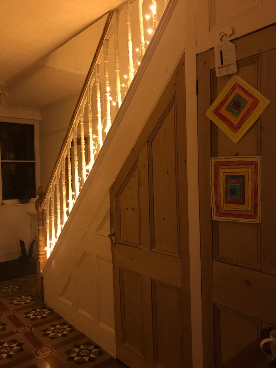 a picture of the side of a staircase, lit by fairylights