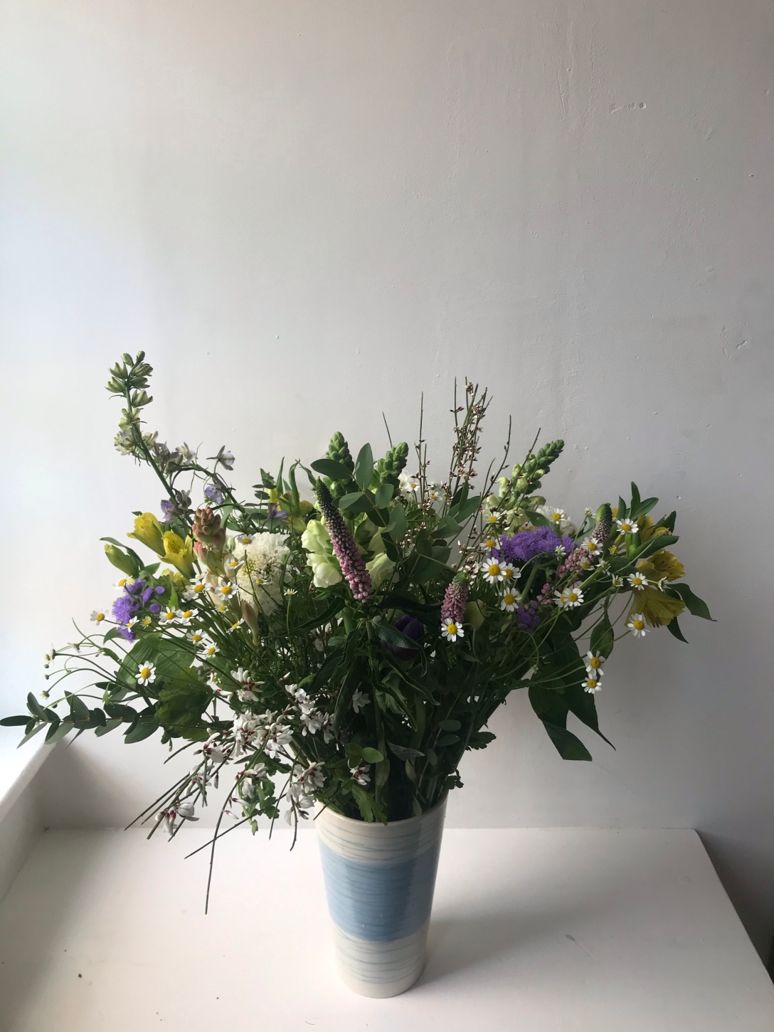The image is of various different types of flowers in a small blue and white vase