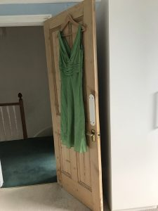 The image is of a green silk dress on a coat hanger, hanging on the back of a wooden door.